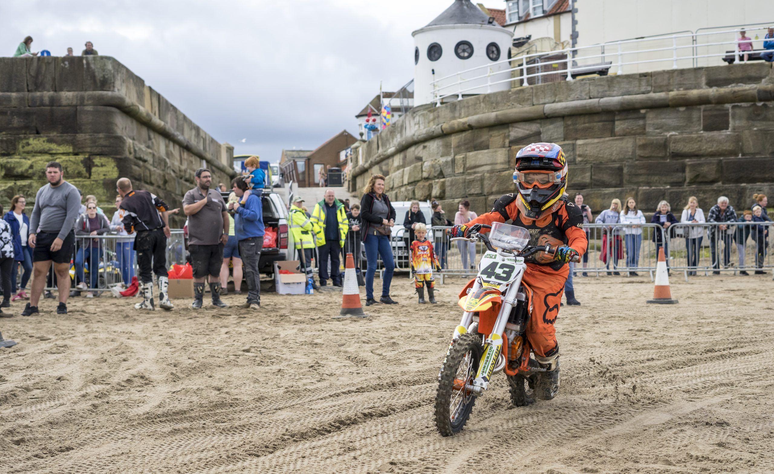 a motor bike racing on Whitby beach with a large crowd watching