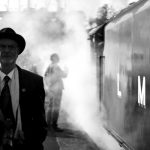 on a train station platform with a steam train