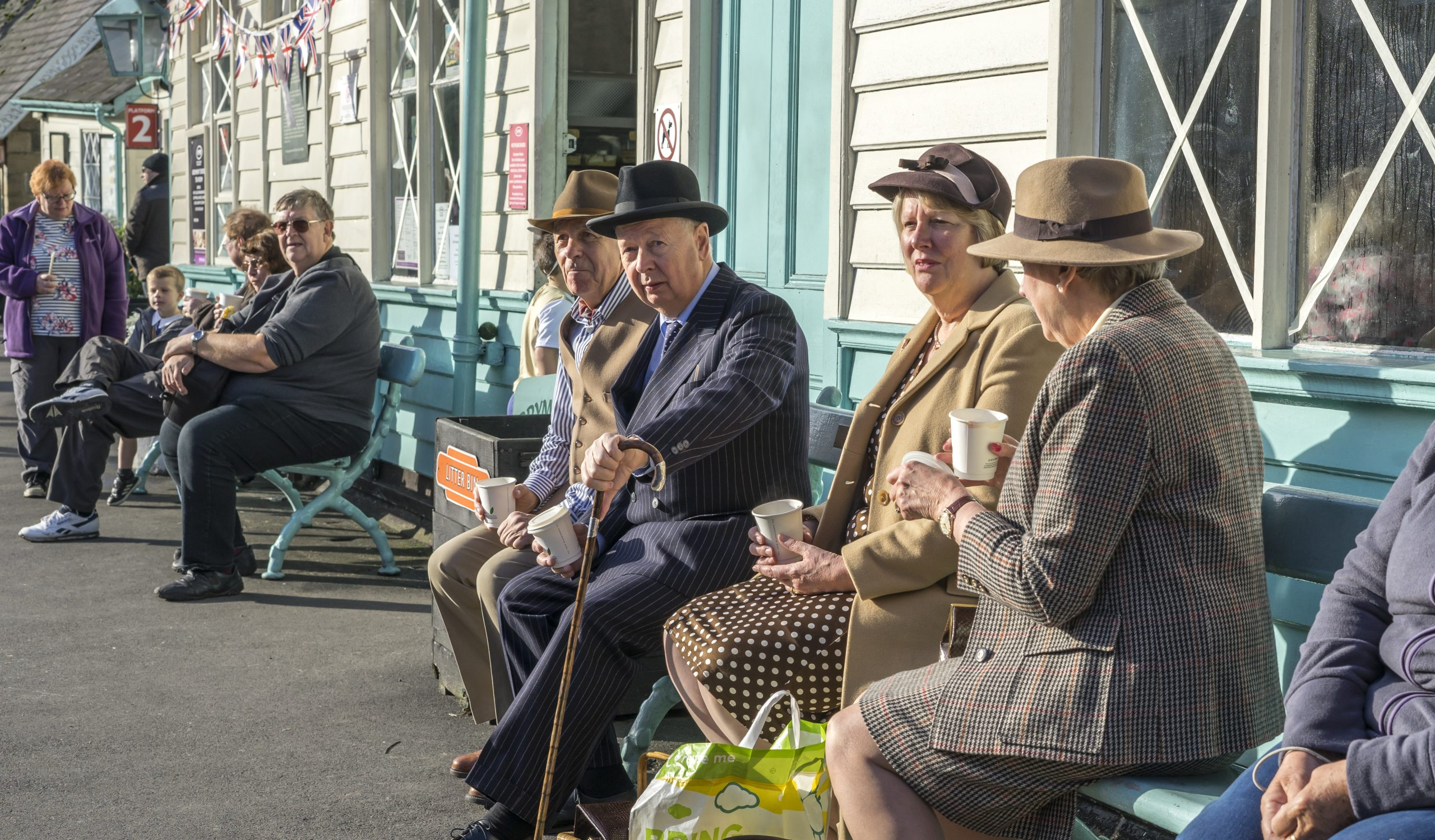 passengers dressed in 1940's style sat on a train station bench