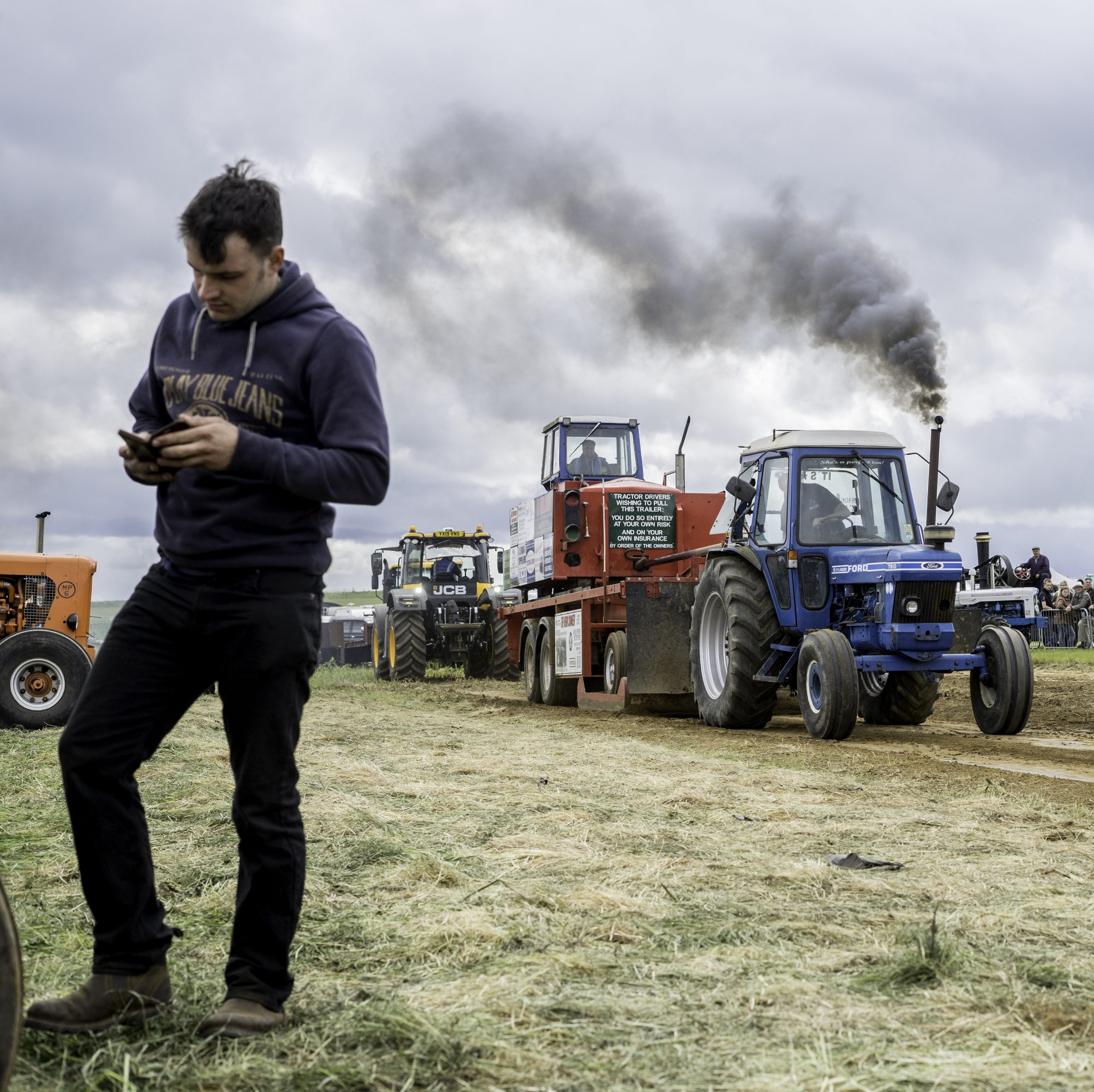 man looking at his phone with tractor pulling in the background